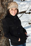 Happy woman in winter forest. Portrait of a young woman standing in snowy winter forest, wearing a cap, black coat, jeans, white boots, standing by a tree Stock Photos