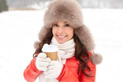 Happy woman in winter fur hat with coffee outdoors Stock Photography