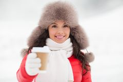 Happy woman in winter fur hat with coffee outdoors Royalty Free Stock Images