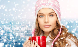 Happy woman in winter hat with cup over snowy city Royalty Free Stock Images