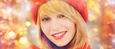 Happy woman in winter hat and scarf over lights. Winter, people, christmas and holidays concept - close up of happy smiling woman in red hat and scarf over royalty free stock photos
