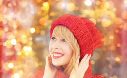 Happy woman in winter hat and scarf over lights. Winter, people, christmas and holidays concept - happy smiling woman in red hat and scarf over lights background royalty free stock photos