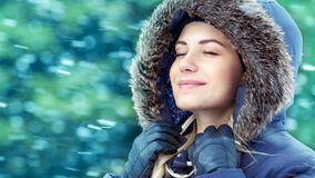 Happy woman in winter park. Portrait of a nice girl in winter park, with closed eyes enjoying falling snow, wearing warm coat with fur hood, happy wintertime Stock Image