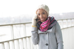 Happy woman in winter wear using cell phone outdoors Royalty Free Stock Photo