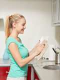 Happy woman wiping dishes at home kitchen Royalty Free Stock Images