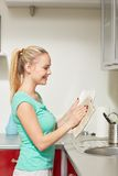 Happy woman wiping dishes at home kitchen Stock Photography