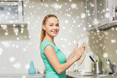 Happy woman wiping dishes at home kitchen Stock Photo