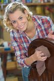 Happy woman wiping dust from wooden furniture Stock Image
