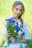 Happy woman wit bouquet of chamomiles and cornflowers Stock Photography