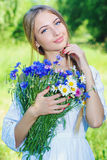 Happy woman wit bouquet of chamomiles and cornflowers Royalty Free Stock Photo