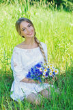 Happy woman wit bouquet of chamomiles and cornflowers Royalty Free Stock Photos