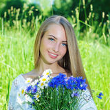 Happy woman wit bouquet of chamomiles and cornflowers Royalty Free Stock Image