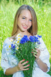Happy woman wit bouquet of chamomiles and cornflowers Stock Photos