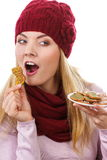 Happy woman in woolen cap and shawl eating gingerbread cookies, white background, christmas time Royalty Free Stock Image