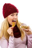 Happy woman in woolen cap and shawl eating gingerbread cookies, white background, christmas time Stock Photography