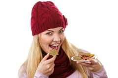 Happy woman in woolen cap and shawl eating gingerbread cookies, white background, christmas time Royalty Free Stock Images