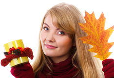 Happy woman in woolen gloves with decorated cup of tea and autumnal leaf, autumn decoration Royalty Free Stock Images