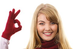 Happy woman in woolen gloves showing sign ok, positive emotions. Happy woman wearing woolen gloves and shawl, showing sign ok, approval of offer or situation Royalty Free Stock Image