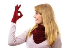 Happy woman in woolen gloves showing sign ok, positive emotions. Happy woman wearing woolen gloves and shawl, showing sign ok, approval of offer or situation Royalty Free Stock Photos