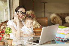 Happy woman working with baby. Happy women smiling and working with baby Royalty Free Stock Images