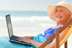 Happy woman working on her laptop Stock Image