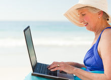 Happy woman working on her laptop at the beach Stock Photo