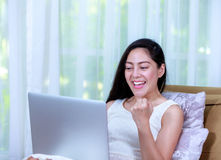 Happy woman working from home with laptop computer. Action of wi Royalty Free Stock Photo