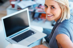 Happy woman working on laptop Stock Photo