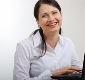 Happy woman working with a laptop. Royalty Free Stock Image