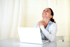 Happy woman working on laptop and looking up. Happy caucasian woman working on laptop and looking up at home indoor Stock Images