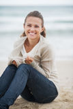 Happy woman wrapping in sweater while sitting on beach Royalty Free Stock Photo