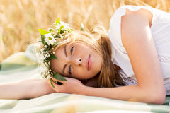 Happy woman in wreath of flowers on cereal field Royalty Free Stock Photo