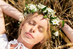 Happy woman in wreath of flowers lying on straw Stock Images