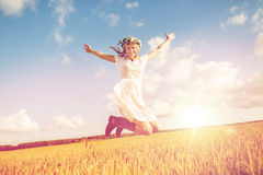 Happy woman in wreath jumping on cereal field. Happiness, nature, summer holidays, vacation and people concept - smiling young woman in wreath of flowers and Stock Images