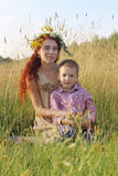 Happy woman in wreath and little son sit in dry grass Stock Photo