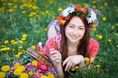 Happy woman with wreath lying on a meadow with a bouquet of flowers Stock Photography