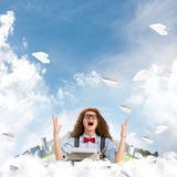 Creative inspiration of young female writer. Happy woman writer in hat and eyeglasses using typing machine while sitting at the table among flying paper planes stock photos