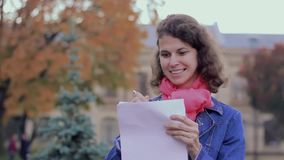 Happy woman writer takes notes on paper while walking in the park