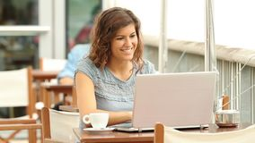 Woman writing in a laptop in a coffee shop. Happy woman writing entering data in a laptop in a coffee shop stock video