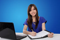 Happy woman writing on notebook, on blue background Stock Photo