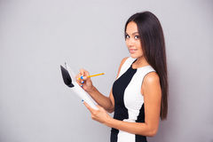 Happy woman writing notes in notepad Royalty Free Stock Image
