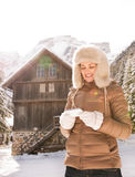 Happy woman writing sms while standing near cosy mountain house Royalty Free Stock Photos