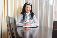 Happy woman writing at table Stock Photography
