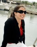 Happy woman on yacht. Happy young woman with sunglasses on boat, yacht marina in background Royalty Free Stock Image