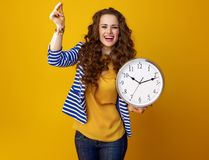 Happy woman on yellow background with clock snapping fingers. Happy modern woman with long wavy brunette hair on yellow background with clock snapping fingers Royalty Free Stock Photos