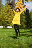 Happy woman in yellow coat jumping in autumn park Royalty Free Stock Images