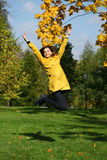 Happy woman in yellow coat jumping in autumn park Royalty Free Stock Image