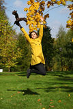 Happy woman in yellow coat jumping in autumn park Royalty Free Stock Photo