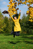 Happy woman in yellow coat jumping in autumn park Stock Photos