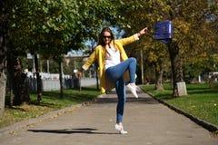 Happy woman in yellow coat walking autumn street Stock Photo